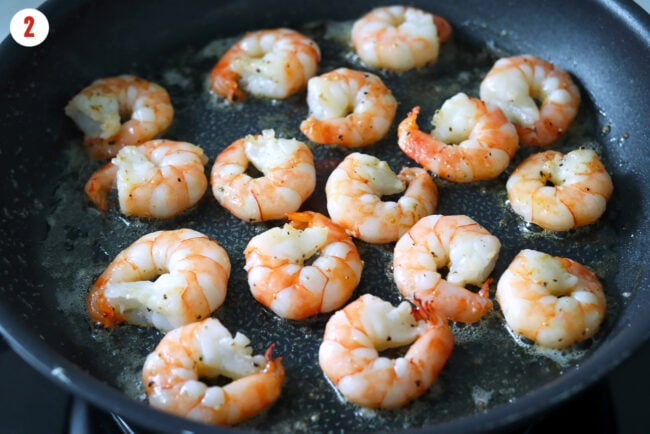 Prawns cooking in butter in a skillet.