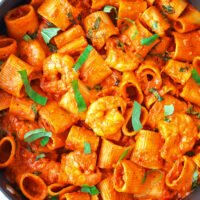 """Top view of black pan with tube-shaped pasta and prawns in tomato sauce. Text overlay """"Spicy Vodka Pasta with Juicy Jumbo Prawns"""" and """"thatspicychick.com""""."""