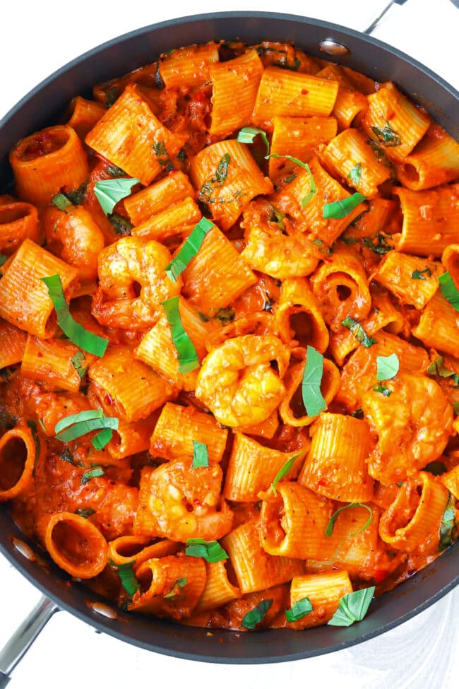 Top view of Spicy Vodka Pasta with Prawns in a large black pan.