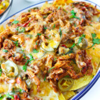 "Close-up of chicken nachos on an oval plate. Text overlay ""Thai Basil Chicken Nachos"", ""Pad Kra Pow Nachos!"", and ""thatspicychick.com""."
