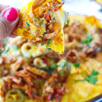 "Hand holding up a chicken nacho. Text overlay ""Thai Basil Chicken Nachos"", ""Pad Kra Pow Nachos!"", and ""thatspicychick.com""."