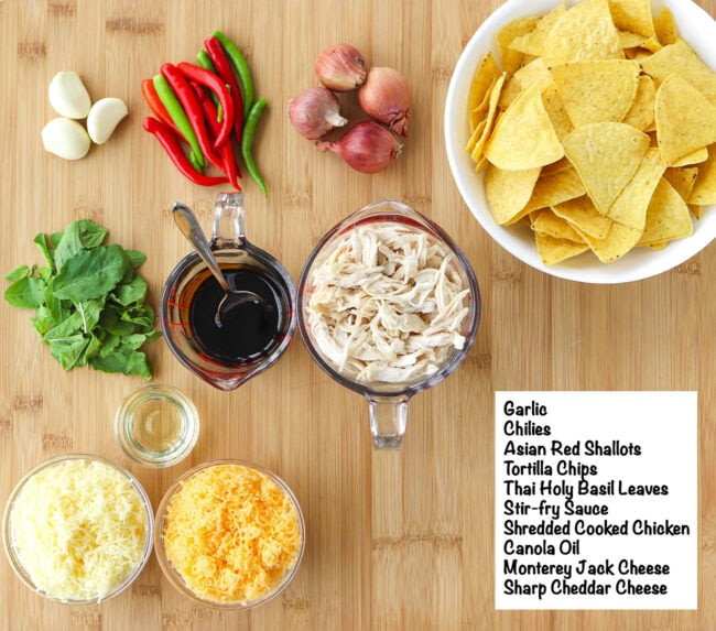 Labeled ingredients for Thai Basil Chicken Nachos on a wooden board.