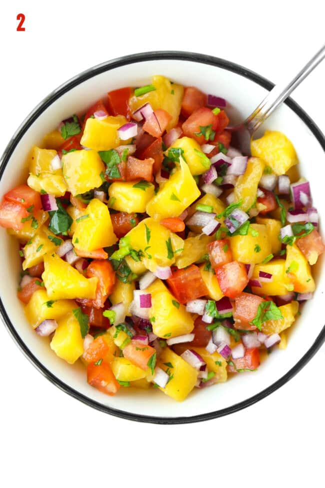 Mango salsa in a bowl with a spoon.