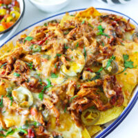 "Close-up front view of nachos on a plate. Text overlay ""Thai Basil Chicken Nachos"", ""With a Refreshing Mango Salsa!"", and ""thatspicychick.com""."