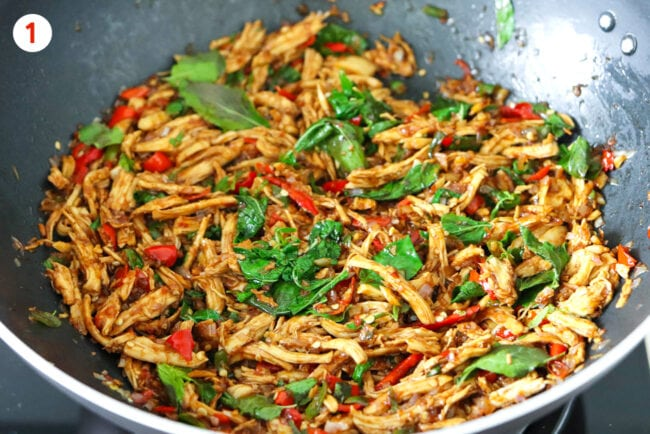 Thai basil shredded chicken in a wok on the stovetop.