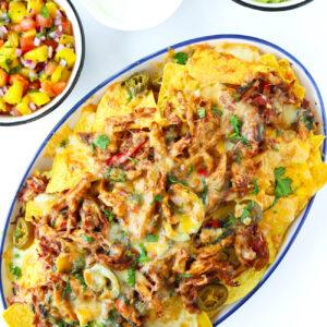 Plate with Thai Basil Chicken Nachos. Bowls with mango salsa, sour cream, and guacamole behind.