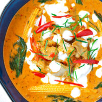 """Top view of chicken curry in blue serving bowl. Text overlay """"Thai Panang Chicken Curry"""", """"Restaurant Style!"""", and """"thatspicychick.com""""."""