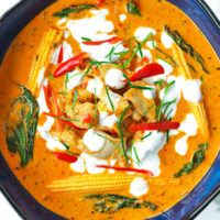 Bowl with panang chicken curry garnished with coconut cream, chilies, and kaffir lime leave strips.