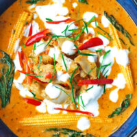 Close-up of bowl with panang chicken curry garnished with coconut cream, chilies, and kaffir lime leave strips.