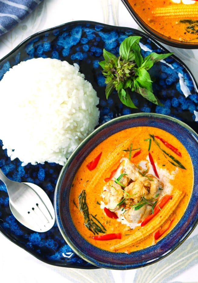 Top view of plate with bowl of panang chicken curry, utensils, and steamed rice.