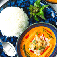 """Top view of small dish with chicken curry on a plate with rice and utensils. Text overlay """"Thai Panang Chicken Curry"""", """"Quick & Easy 