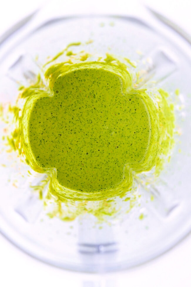 Blended green sauce in blender jug.