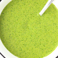 """Close-up top view of bowl with green sauce and a spoon. Text overlay """"Cilantro and Mint Sauce"""", """"For Kebabs + Kathi Rolls + Dipping"""", and """"thatspicychick.com""""."""