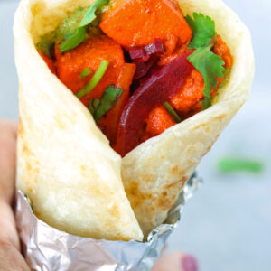 Hand holding up a paneer tikka kathi roll wrapped in foil.