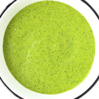 """Bowl with green sauce. Text overlay """"Cilantro and Mint Sauce"""", """"For Kebabs + Kathi Rolls & More!"""", and """"thatspicychick.com""""."""