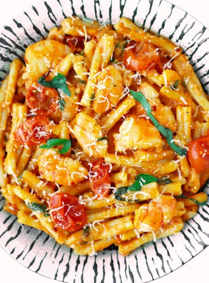 Close-up top view of creamy rosé pasta with prawns on a plate.