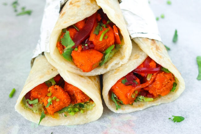 Front view of three stacked paneer tikka kathi rolls on sheet of parchment paper.