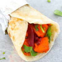 """A paneer kathi roll on parchment paper. Text overlay """"Paneer Tikka Kathi Rolls"""", """"Tasty Indian Street Food Wraps!"""", and """"thatspicychick.com""""."""
