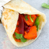 Close-up side view of a paneer tikka kathi roll with the back part wrapped in foil.