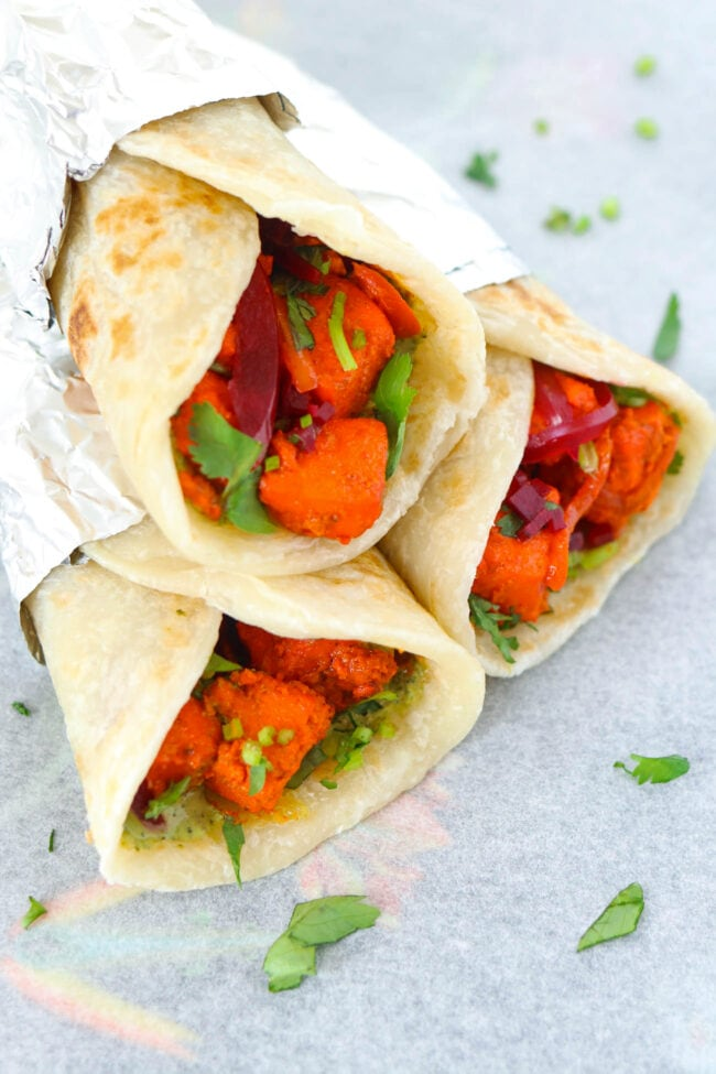 Front side view of three stacked paneer tikka kathi rolls.