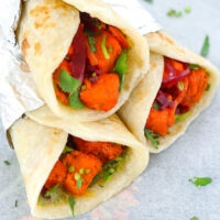 """Close-up of stacked paneer kathi rolls on parchment paper. Text overlay """"Paneer Tikka Kathi Rolls"""", """"Easy 30-Minute Spicy Paneer Wraps!"""", and """"thatspicychick.com""""."""