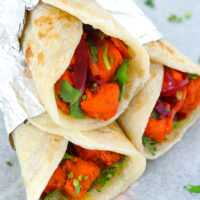 """Stacked paneer kathi rolls on parchment paper. Text overlay """"Paneer Tikka Kathi Rolls"""", """"Quick Indian Street Food Wraps!"""", and """"thatspicychick.com""""."""