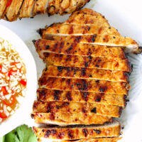 """Close-up top view of sliced grilled pork steak on a plate. Text overlay """"Vietnamese Grilled Pork Steaks"""", """"thatspicychick.com"""", and """"With Nuoc Cham Dipping Sauce""""."""