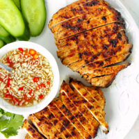 """Top view of sliced grilled pork steaks on a plate. Text overlay """"Vietnamese Grilled Pork Steaks"""", """"thatspicychick.com"""", and """"With Nuoc Cham Dipping Sauce""""."""
