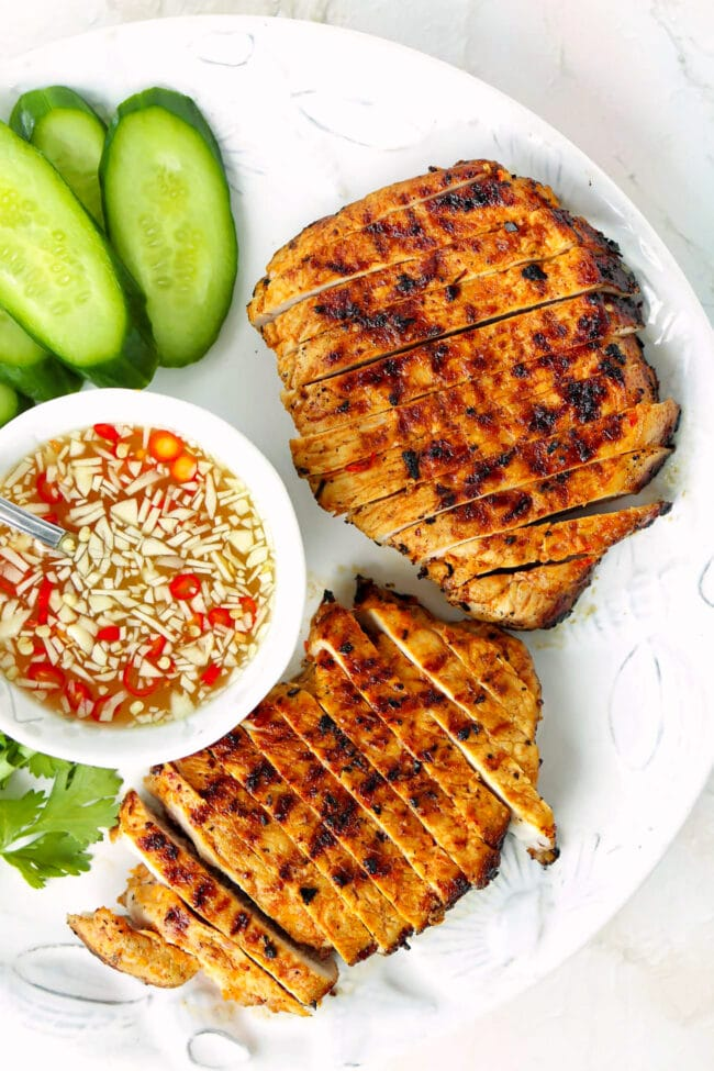 Grilled pork steaks on a plate with a bowl with nuoc cham dipping sauce.