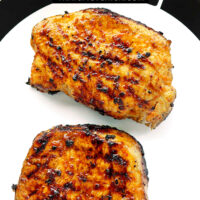 """Two grilled pork steaks resting on a plate. Text overlay """"Vietnamese Grilled Pork Steaks"""" and """"thatspicychick.com""""."""