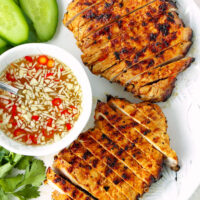 """Sliced grilled pork steaks on a plate with a bowl of nuoc cham sauce. Text overlay """"Vietnamese Grilled Pork Steaks"""", """"thatspicychick.com"""", and """"With Nuoc Cham Dipping Sauce""""."""