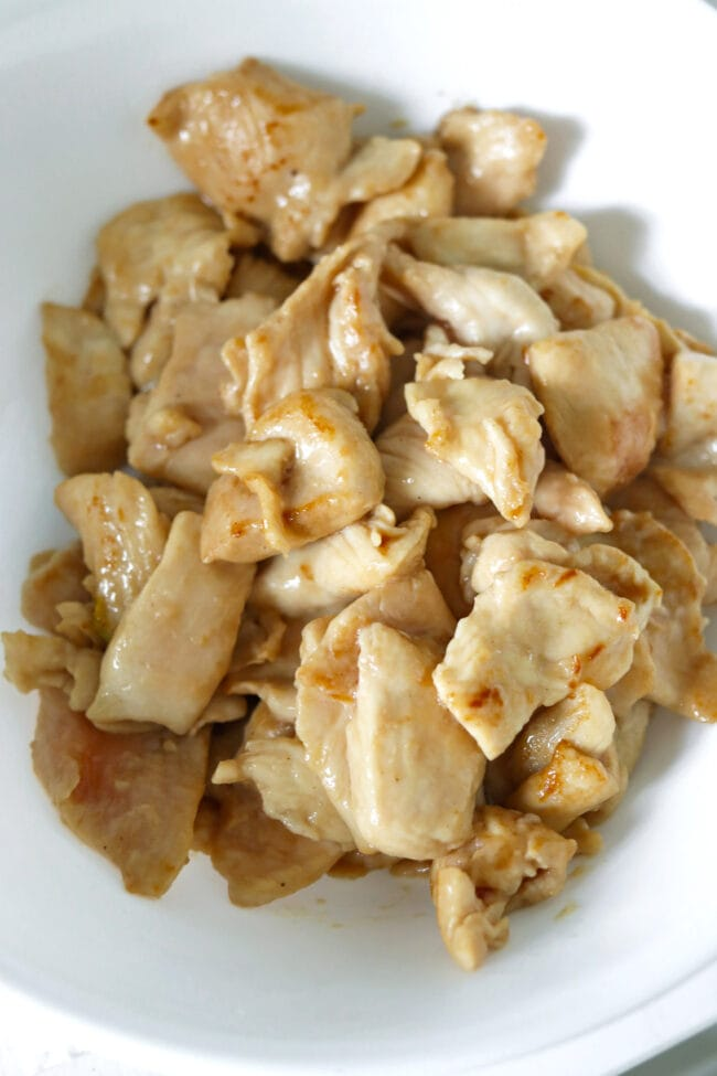 Partially cooked chicken pieces in bowl.