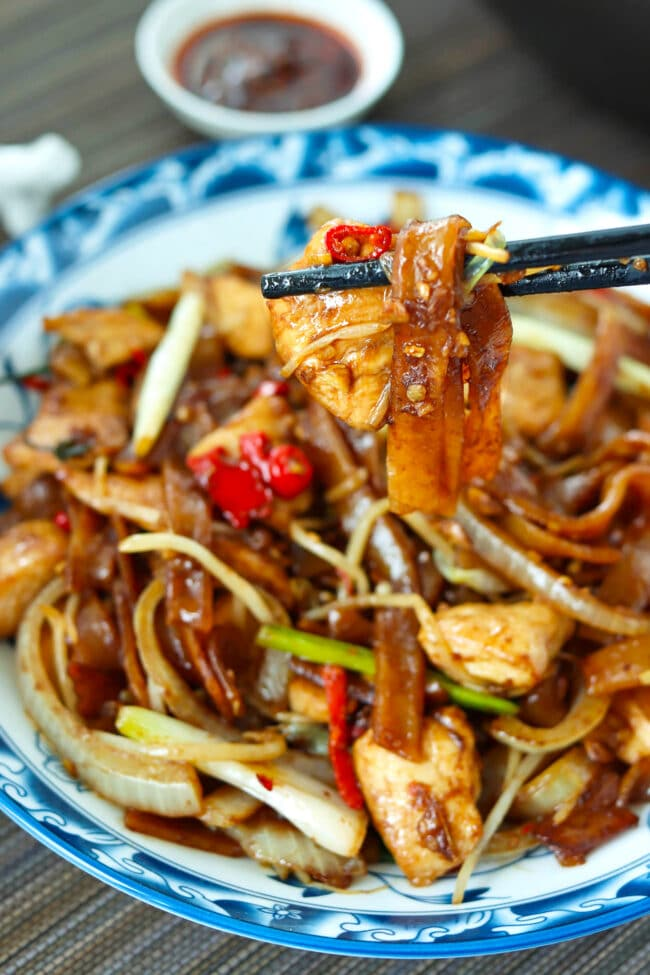 Chopsticks holding up a bite of rice noodles stir-fry above a plate with the noodles.