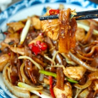 """Chopsticks holding up a bite of rice noodles with a chicken piece above plate. Text overlay """"Chicken Chow Fun"""", """"Cantonese Style Noodles Stir-fry"""", and """"thatspicychick.com""""."""