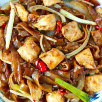 """Close-up top view of stir-fried chicken and rice noodles on a plate. Text overlay """"Chicken Chow Fun"""", """"Cantonese Rice Noodles Stir-fry"""", and """"thatspicychick.com""""."""