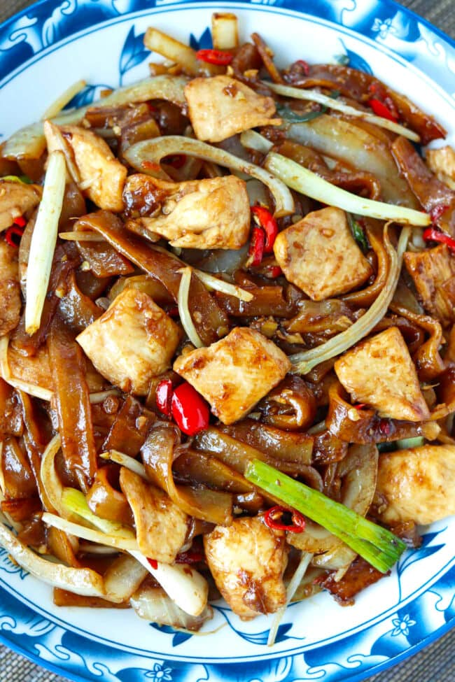 Close-up top view of stir-fried rice noodles and chicken on a plate.