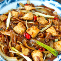 """Front view of stir-fried chicken noodles on a plate. Text overlay """"Chicken Chow Fun"""", """"Easy Cantonese Noodles Stir-fry"""", and """"thatspicychick.com""""."""