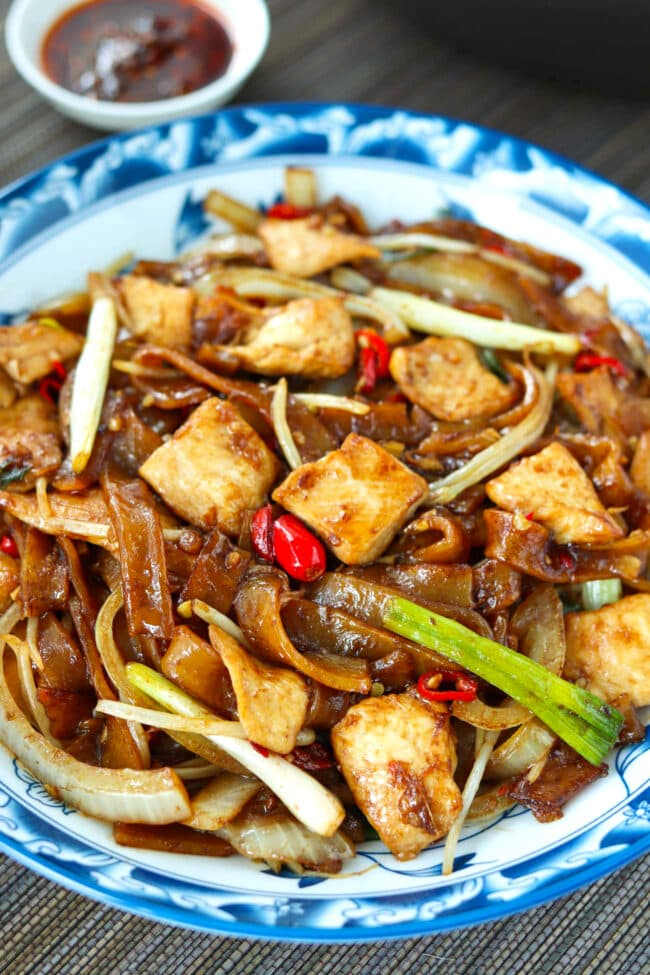 Front view of stir-fried wide rice noodles and chicken on a plate.