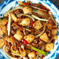 """Top view of stir-fried rice noodles with chicken, onion, chives, bean sprouts, and chilies. Text overlay """"Chicken Chow Fun"""", """"Cantonese Style Noodles Stir-fry"""", and """"thatspicychick.com""""."""