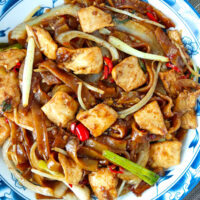Close-up top view of rice noodles and chicken stir-fry on a plate.