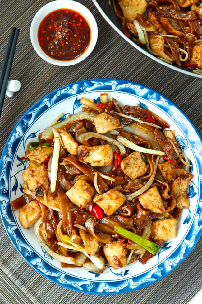 Top view of stir-fried chicken chow fun on a plate and in a wok.