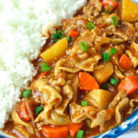 """Close-up front view of curry and rice on plate. Text overlay """"Japanese Pork Belly Curry"""", """"Easy 