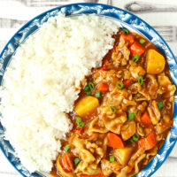 """Top view of curry and rice on a blue rimmed plate. Text overlay """"Japanese Pork Curry"""", """"Easy 40 Minute Recipe"""", and """"thatspicychick.com"""""""