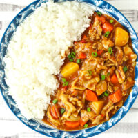 """Blue rimmed plate with curry and rice. Text overlay """"Japanese Pork Curry"""", """"With Thinly Sliced Pork Belly"""", and """"thatspicychick.com"""""""