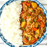 """Close-up overhead view of curry and rice on plate. Text overlay """"Japanese Pork Curry"""", """"With Thinly Sliced Pork Belly"""", and """"thatspicychick.com"""""""