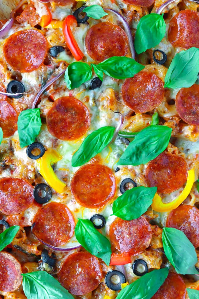 Super close-up of baked cheese, pepperoni slices, sliced olives, red onion, bell peppers, and basil leaves.