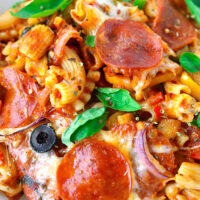 """Close-up of baked pasta dish with pepperoni on a plate. Text overlay """"Pizza Pasta Bake"""", """"Easy 
