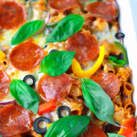 """Close-up front view of baked cheesy pasta with pepperoni and fresh basil in baking dish. Text overlay """"Pizza Pasta Bake"""", """"Easy 