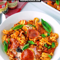 """Front view of baked pasta dish with pepperoni and pizza toppings. Text overlay """"Pizza Pasta Bake"""", """"A delicious dinner the whole family will love!"""", and """"thatspicychick.com""""."""