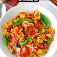 """Top view of pasta bake on a plate with pepperoni and veggie pizza toppings. Text overlay """"Pizza Pasta Bake"""", """"Customizable with your favorite pizza toppings!"""", and """"thatspicychick.com"""""""